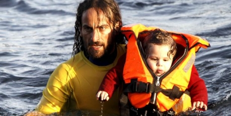 https://avaazimages.s3.amazonaws.com/18288_A-volunteer-lifeguard-carries-a-baby-as-a-half-sunken-catamaran_1_459x230.jpg